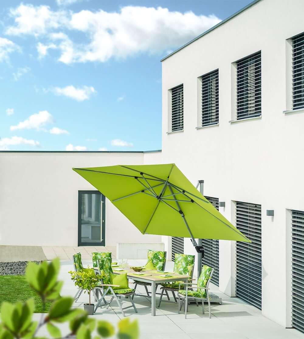 schwenkbarer sonnenschirm in grün auf einer terrasse