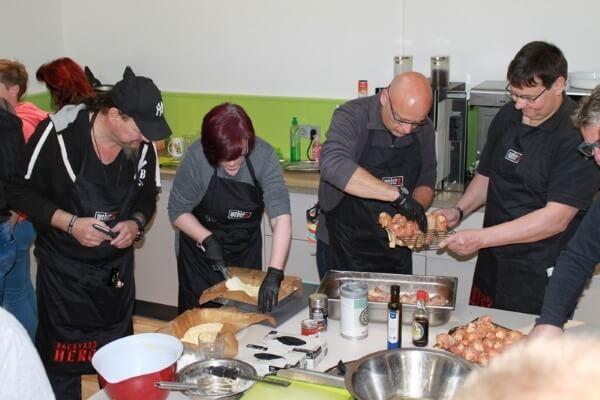 Teilnehmer und Teilnehmerin eines Weber Grillseminars bei der Zubereitung