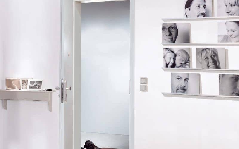 weisse Wohnungseingangstuer mit weissen Waenden mit Portraetbildern
